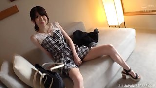 Cute Asian masturbates alone using her hand and a big dildo on the sofa